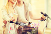 Couple holding coffee and riding bicycle — Stok fotoğraf