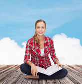 Smiling young woman sitting on floor with book — Stock Photo
