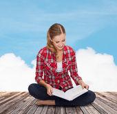 улыбается молодой женщины, сидя на полу с книгой — Стоковое фото