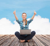 Smiling woman with laptop and showing thumbs up — Foto de Stock