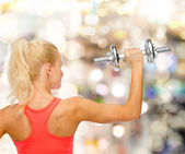 Sporty woman with heavy steel dumbbell from back — Stock Photo