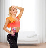Smiling sporty woman with towel and water bottle — Stock Photo