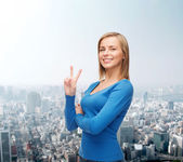 Smiling teenage girl showing v-sign with hand — Stock Photo