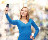 Woman taking self picture with smartphone camera — Stock Photo