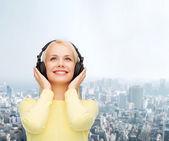ヘッドフォンを持つ若い女性の笑みを浮かべてください。 — ストック写真