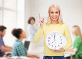 Student with wall clock and finger up — Stock Photo