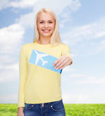 Smiling young woman with airplane ticket — Stockfoto