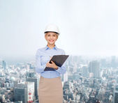 Smiling businesswoman in helmet with clipboard — Foto Stock