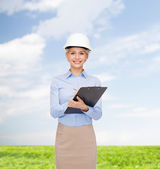 Smiling businesswoman in helmet with clipboard — Stock Photo