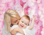 Glad mamma kysser leende baby — Stockfoto