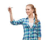 Smiling young woman writing on virtual screen — Stock Photo