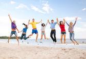 集团的朋友在沙滩上跳跃 — 图库照片