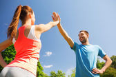Two smiling people making high five outdoors — Foto Stock