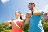 Smiling people with heart rate watches outdoors — Stock Photo