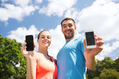 Two smiling people with smartphones outdoors — Foto de Stock
