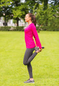 Smiling black woman stretching leg outdoors — Stock Photo