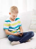 Smiling little boy with smartphone at home — Stock Photo