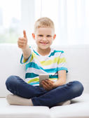 Smiling boy with smartphone showing thumbs up — Stock Photo
