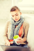 Diseased woman in scarf using laptop at home — Stock Photo