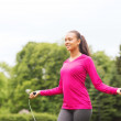 Smiling woman exercising with jump-rope outdoors — Stock Photo #50022861