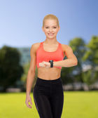 Smiling woman with heart rate monitor on hand — Stockfoto