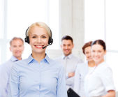 Friendly female helpline operator with headphones — Stock Photo