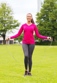 Smiling woman exercising with jump-rope outdoors — Foto Stock