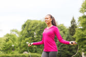 Smiling woman exercising with jump-rope outdoors — Stockfoto