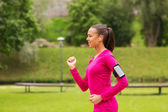 Smiling young woman running outdoors — Stock Photo