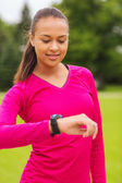 Smiling young woman with heart rate watch — Stockfoto