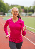 Smiling young woman running on track outdoors — Stock Photo