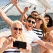 Smiling friends sitting on yacht deck — Stock Photo #50087095