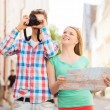 Smiling couple with map and photo camera in city — Stock Photo #50089035