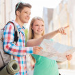 Smiling couple with map and backpack in city — Stock Photo #50089135