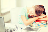 Tired student sleeping on stock of books — Stock Photo
