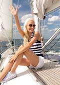 Sonriente a joven mujer sentada en la cubierta del yate — Foto de Stock