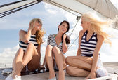 Smiling girlfriends sitting on yacht deck — Stockfoto