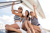 Smiling girlfriends sitting on yacht deck — 图库照片