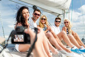 Smiling friends photographing on yacht — Photo