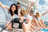 Smiling friends photographing on yacht — Stock Photo