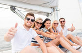 Smiling friends on yacht showing thumbs up — Stock Photo