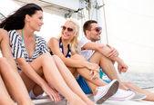Amis souriant assis sur le yacht pont — Photo