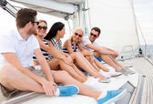 Smiling friends sitting on yacht deck — Stock Photo