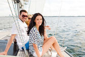 Smiling friends sitting on yacht deck — Stock fotografie