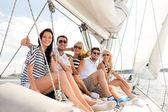Smiling friends sitting on yacht deck — Zdjęcie stockowe