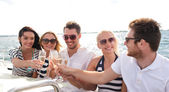 Smiling friends with glasses of champagne on yacht — Stock Photo