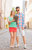 Smiling couple with tablet pc in city — Stock fotografie