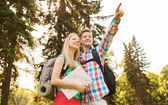 Smiling couple with map and backpack in nature — Stock Photo
