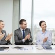 Business team with laptop clapping hands — Stock Photo