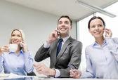 Business team with smartphones having conversation — Foto de Stock